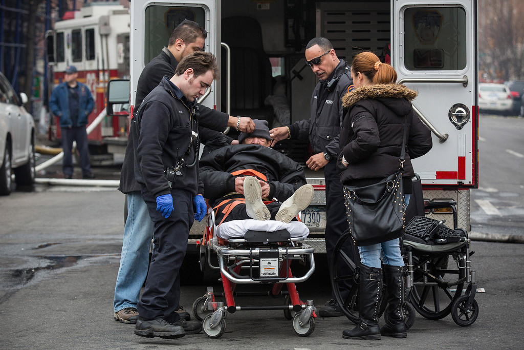 . A man is loaded into an ambulance on a stretcher hours after a two-building collapse on March 12, 2014 in New York City.   (Photo by Andrew Burton/Getty Images)