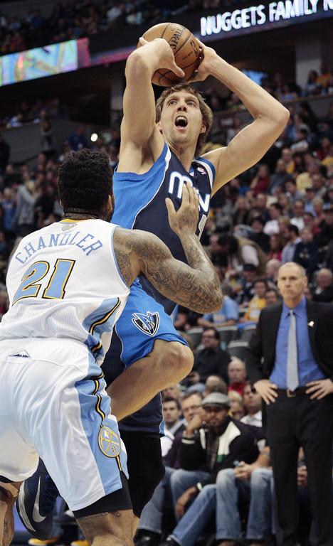 . Dallas Mavericks forward Dirk Nowitzki (41) shoots against Denver Nuggets forward Wilson Chandler (21) during the first quarter of an NBA basketball game in Denver on Saturday, Nov. 23, 2013. (AP Photo/Joe Mahoney)