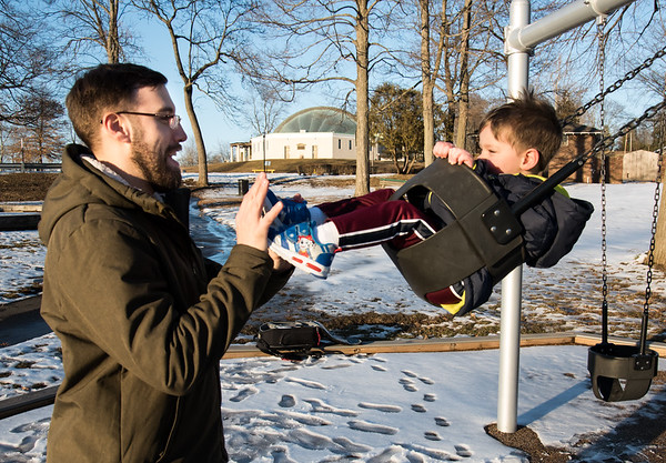 02/21/19 Wesley Bunnell | Staff Jeremy Lee stands in front of his son Fox , age 3, as he pushes him on the swings at Walnut Hill Park on Thursday afternoon.