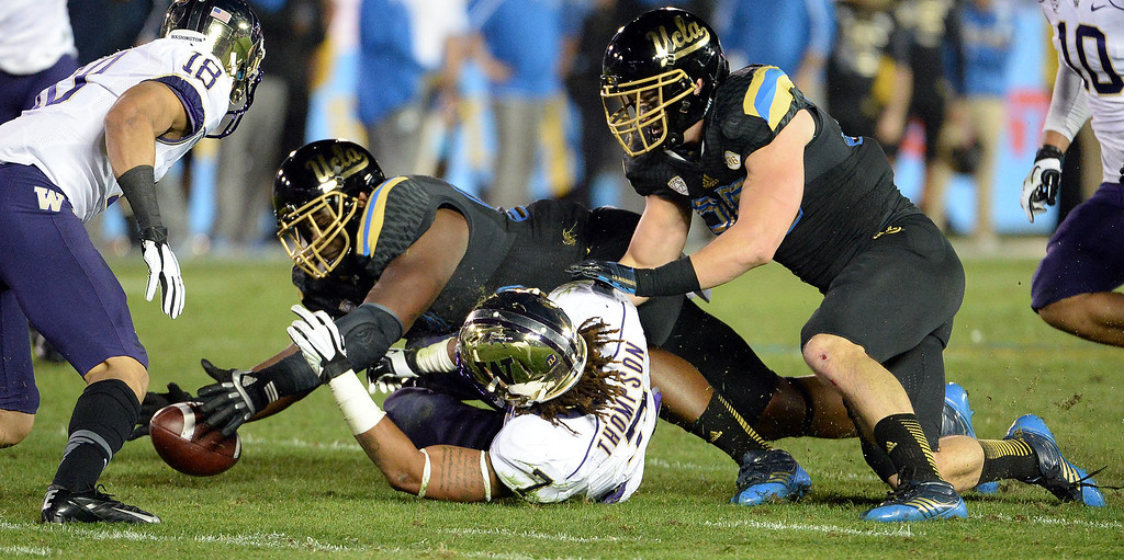 . UCLA Bruins recovers a Washington Huskies fumble during the first half of their college football game in the Rose Bowl in Pasadena, Calif., on Friday, Nov. 15, 2013.   (Keith Birmingham Pasadena Star-News)