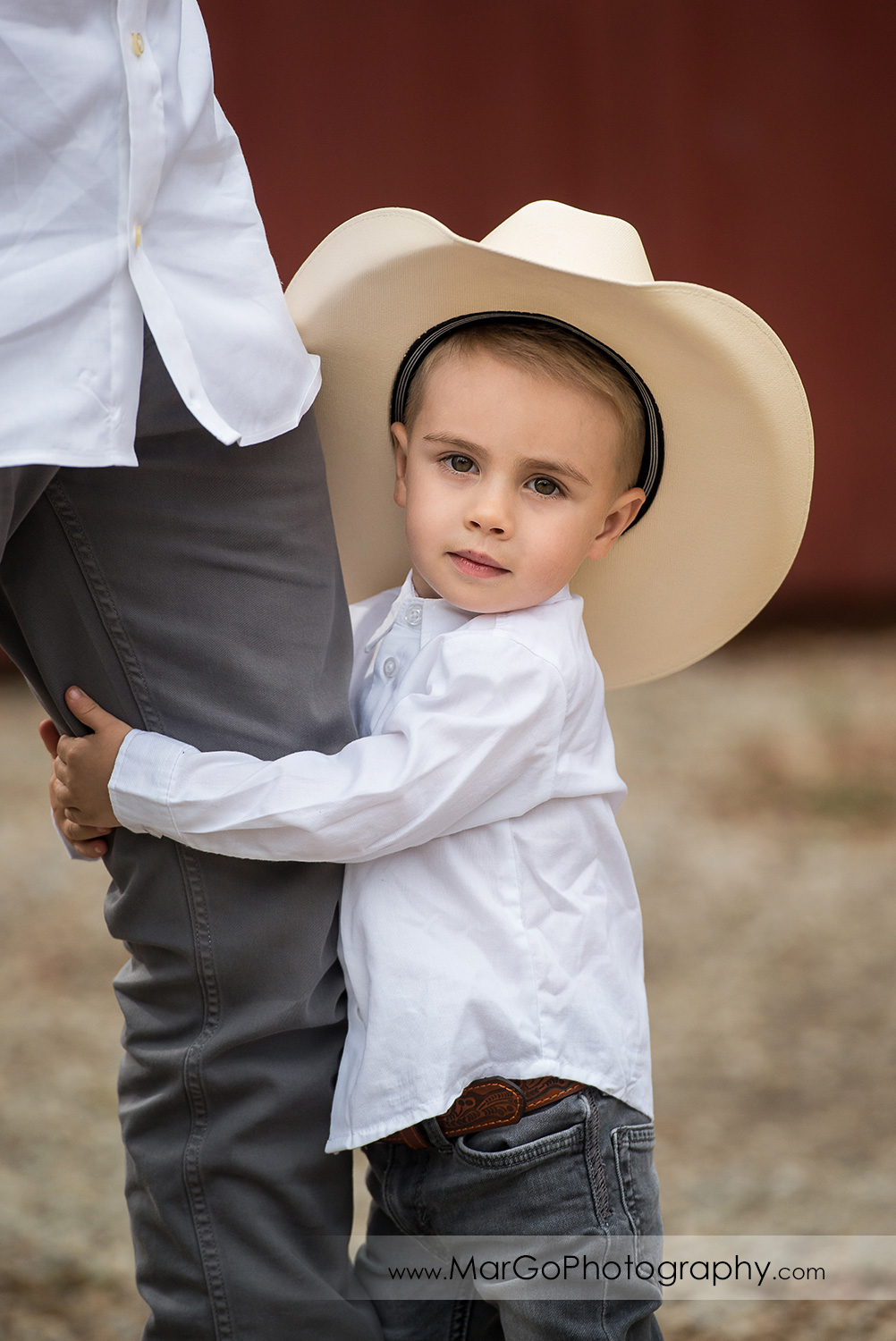 portrait of little boy in white shirt, gray jeans and cowboy hat holding dad's leg in Shinn Historical Park and Arboretum in Fremont