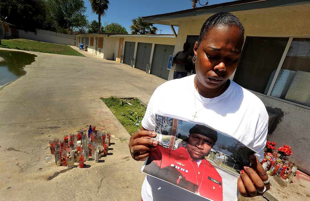 ". Ganesha Boone, 35, holds a picture of boyfriend Jerald Lee Belton at a memorial site along North Sierra Way in San Bernardino April 18, 2013.  ""He was taken away too soon,\"" said Boone. \""There are so many people that\'s hurting behind losing him.\""  (Photo by Gabriel Luis Acosta/The Sun)"
