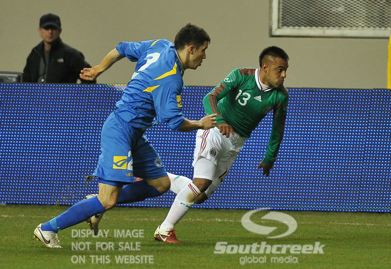 Mexico's Forward Edgar Pacheco (#13) and Bosnia-Herzegovina's Defender Mensur Mujdza (#2) give chase after the ball during Soccer action between Bosnia-Herzegovina and Mexico.  Mexico defeated Bosnia-Herzegovina 2-0 in the game at the Georgia Dome in Atlanta, GA.