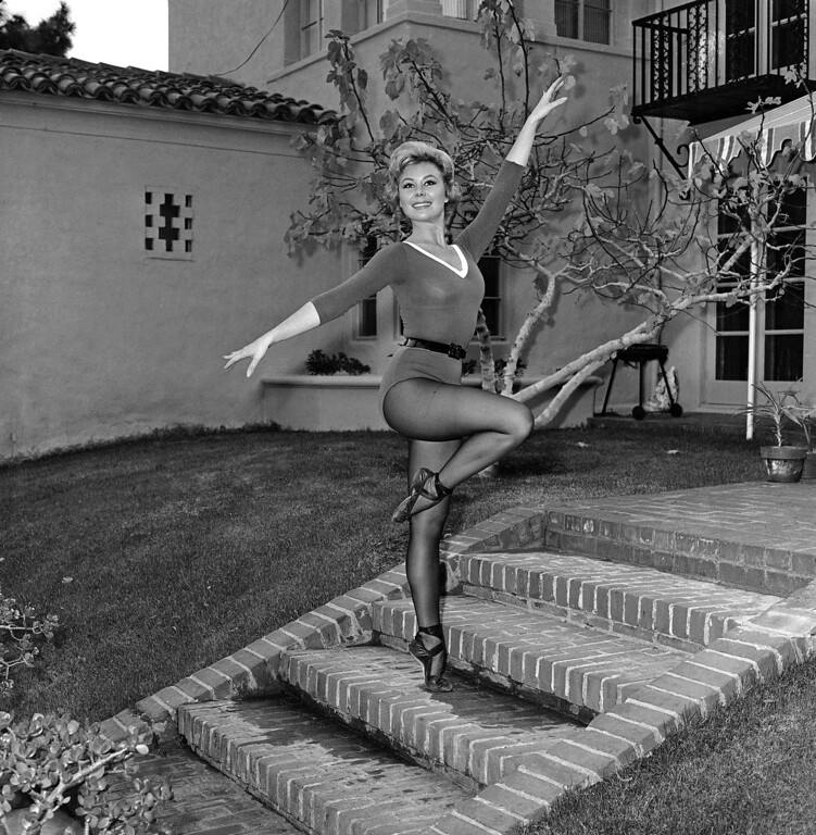 . Dancer-actress Mitzi Gaynor does a two step, two up and two down, on the brick steps outside her home at Beverly Hills, California on Jan. 23, 1961.   She says the on-her-toes steps keep her figure in trim. Something does. (AP Photo)