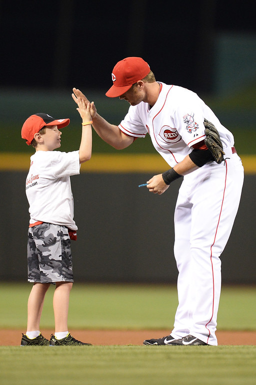 . CINCINNATI, OH - SEPTEMBER 8:  Zack Cozart #2 of the Cincinnati Reds high fives a young fan before the start of the game against the Los Angeles Dodgers at Great American Ball Park on September 8, 2013 in Cincinnati, Ohio.  (Photo by Jamie Sabau/Getty Images)