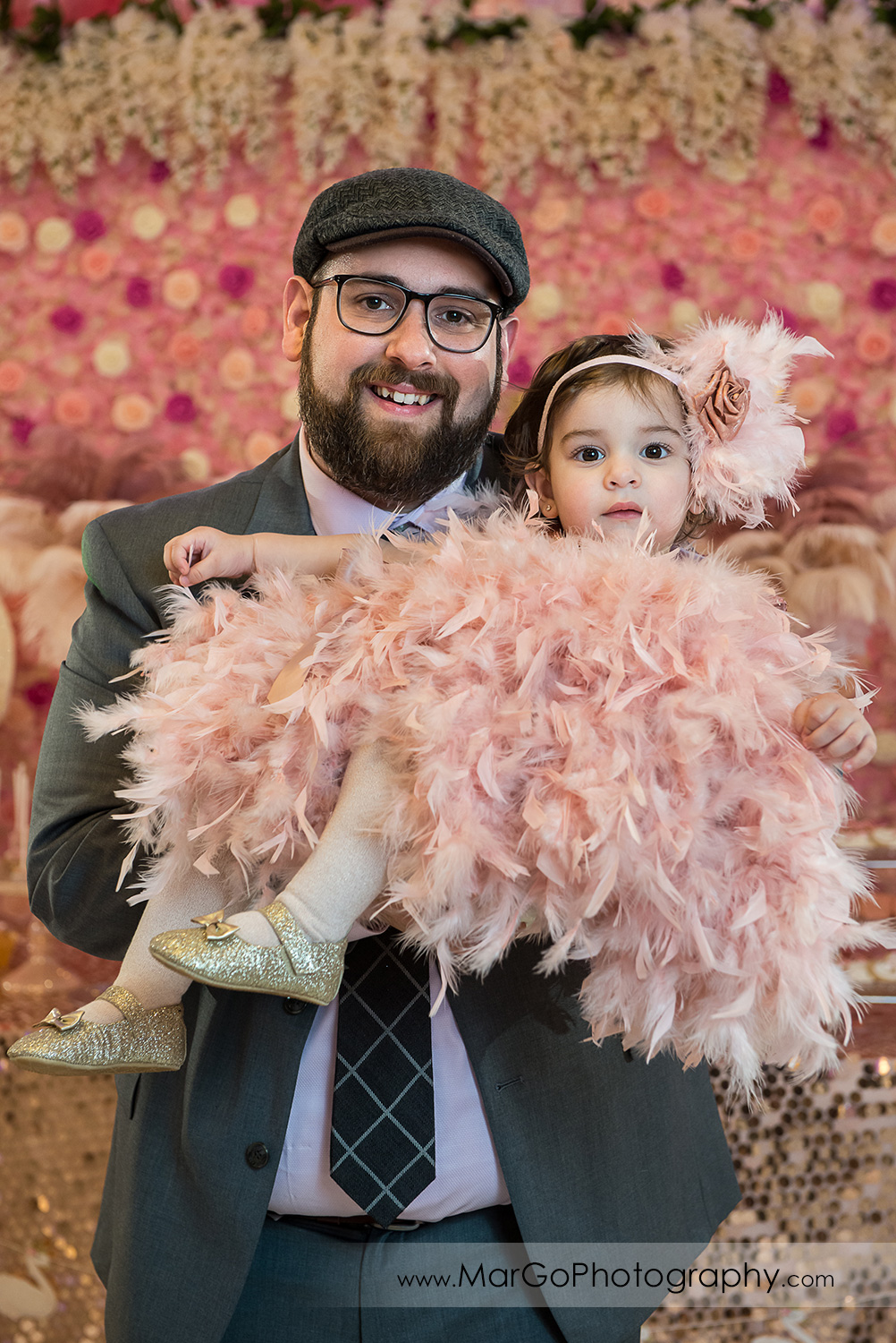 little girl in pink feather dress on her father's arms at Newark Oasis Palace