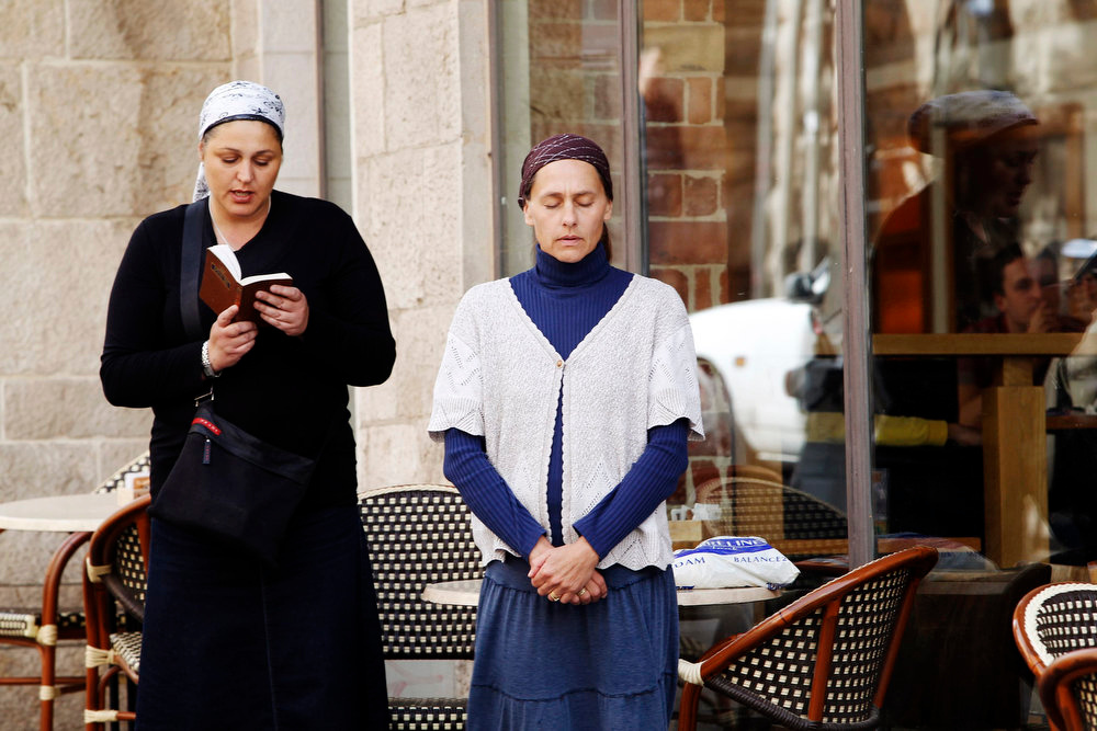 . An Israeli woman stands still while another prays beside her as a two-minute siren marking Holocaust Remembrance Day is sounded in Jerusalem on April 8, 2013. Israel on Monday marks the annual memorial day commemorating the six million Jews killed by the Nazis in the Holocaust during World War Two. REUTERS/Baz Ratner