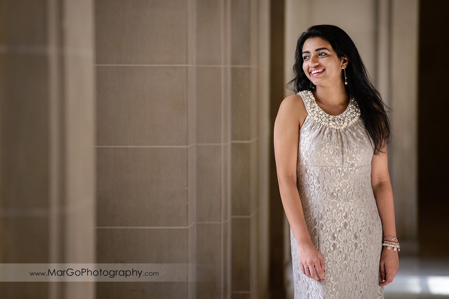 3/4 portrait of woman in beige dress on the third floor of San Francisco City Hall