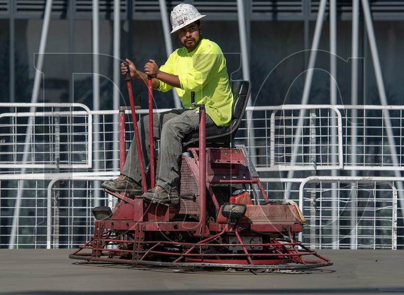 Salvador Greho, a journeyman cement mason with Local 555 and an employee of LaRusso Concrete, operates a riding trowel machine as he and his crew finish a freshly poured concrete post-tensioned deck on the building's fourth floor. (Josh Kulla/DJC)