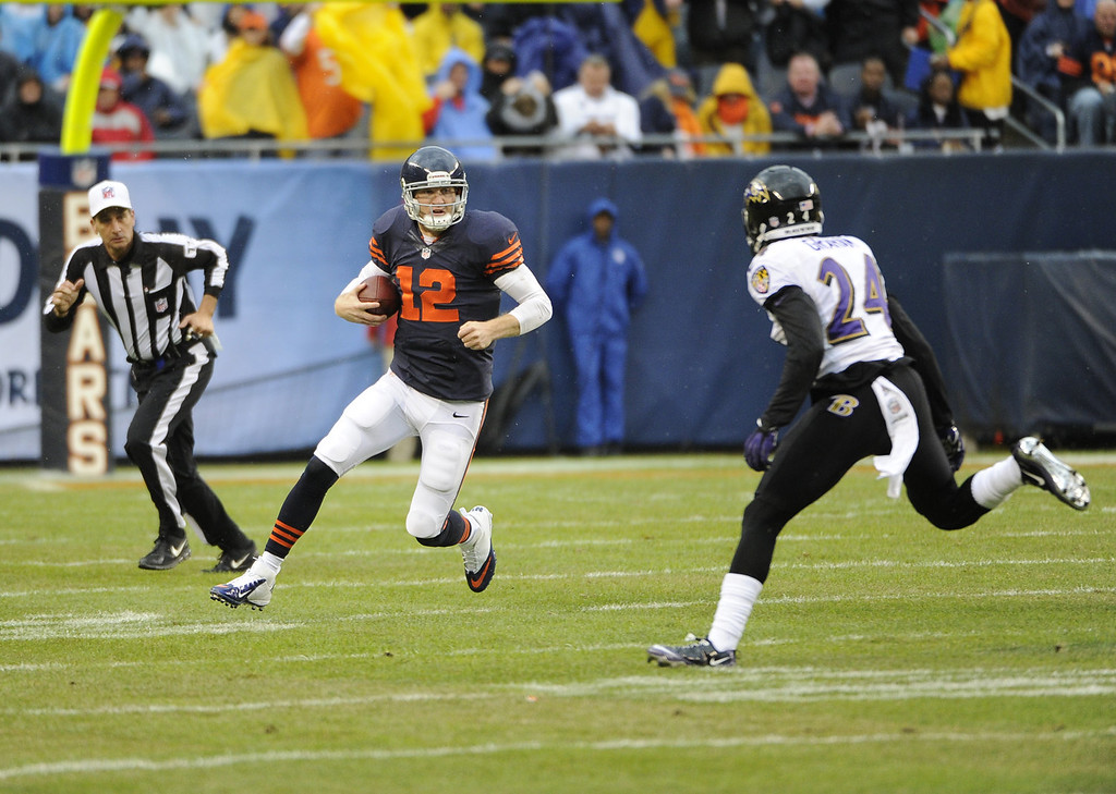 . Josh McCown #12 of the Chicago Bears runs as Corey Graham #24 of the Baltimore Ravens looks to make a tackle during the first quarter on November 17, 2013 at Soldier Field in Chicago, Illinois. (Photo by David Banks/Getty Images)