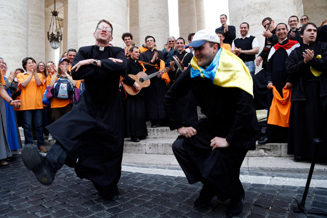 . Two priests, one of them with an Ukrainian flag on his shoulders, dance in St. Peter\'s Square at the Vatican, Saturday, April 26, 2014. Pilgrims and faithful are gathering in Rome to attend Sunday\'s ceremony at the Vatican where Pope Francis will elevate in a solemn ceremony John XXIII and John Paul II to sainthood. (AP Photo/Domenico Stinellis)