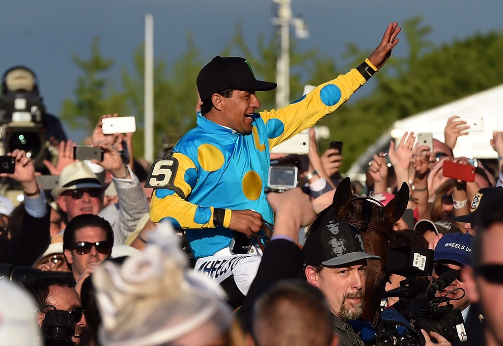 . Victor Espinoza, jockey of American Pharoah, wave as he goes to the winner\'s circle after winning the 147th Belmont Stakes at Belmont Park on June 6, 2015 in Elmont, New York. American Pharoah ended US racing\'s 37-year Triple Crown drought on Saturday with a convincing victory in the Belmont Stakes.  AFP PHOTO  / TIMOTHY A. CLARY/AFP/Getty Images