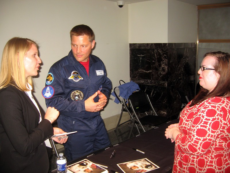 """Jen discusses Doug Wheelock's use of Foursquare in space with NASA Social Media Manager Stephanie Schierholz.  The Foursquare """"NASA Explorer"""" badge is visible on his right sleeve."""