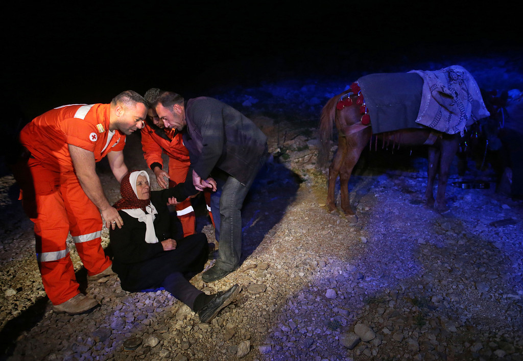 . In this picture taken early Sunday, April 20, 2014, Farizeh Kabalan, 74, who fled her home from the Syrian village of Beit Jinn near the Israeli-occupied Golan Heights, is helped by Lebanese Red Cross volunteers after she descended from the 2,814-meter (9,232-foot) high Mount Hermon  (Jabal el-Sheikh). She sits on the ground waiting to go into the town of Chebaa in southeast Lebanon. Many of the people in Bin Jinn had been displaced several times by the fighting in Syria before fleeing into Lebanon. (AP Photo/Hussein Malla)