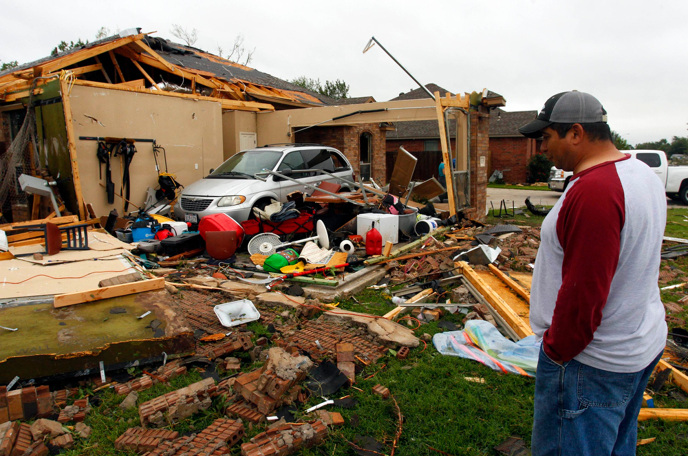 . Pete Alaniz assesses the damage to the garage of his rental home that was destroyed by a tornado in Cleburne, Texas May 16, 2013. At least six people were killed and seven were missing after as many as 10 tornadoes ripped through north-central Texas Wednesday evening, leaving a trail of destruction from the worst severe storm outbreak in the United States so far this year.  REUTERS/Richard Rodriguez
