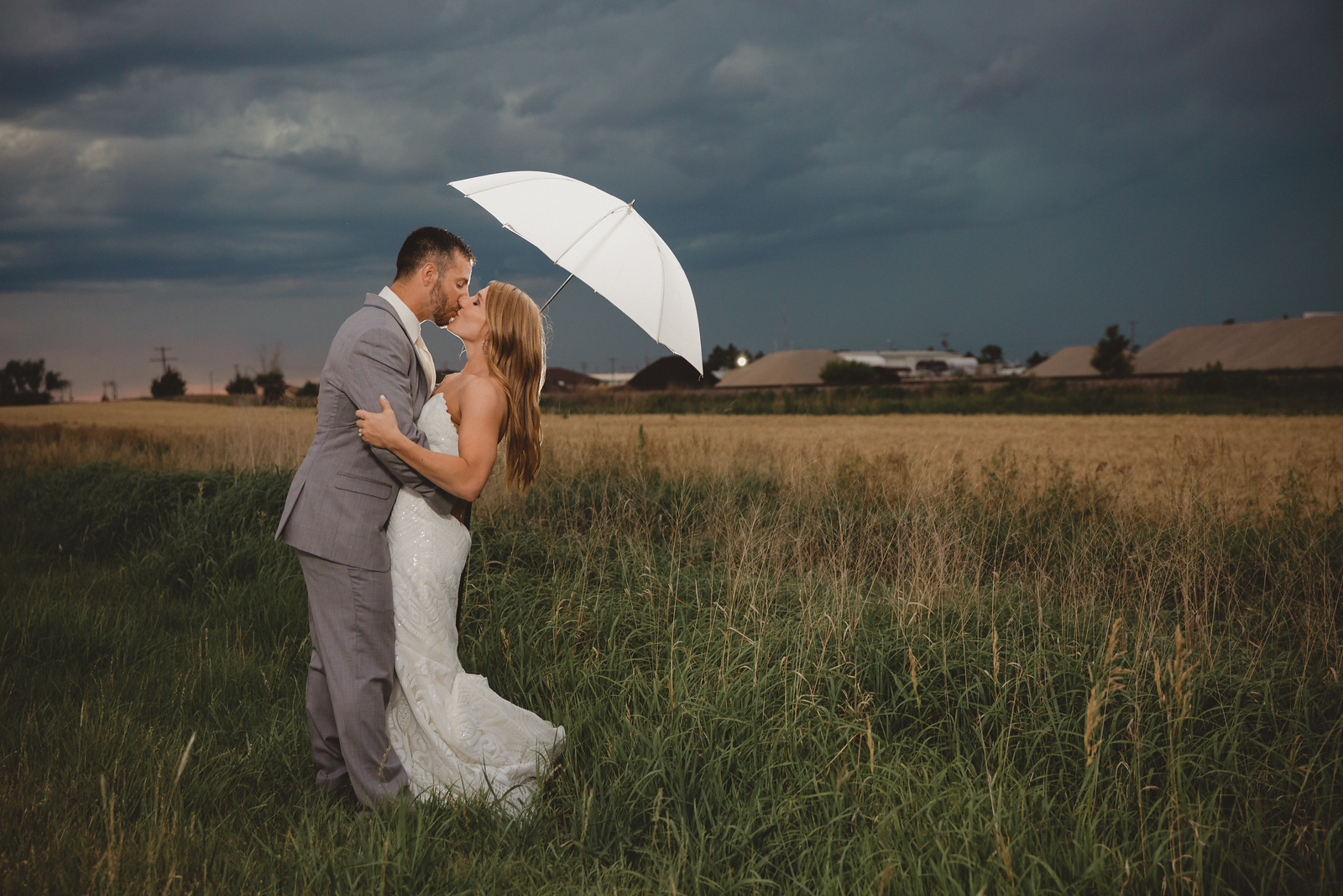 bride and groom share a moment in the rain