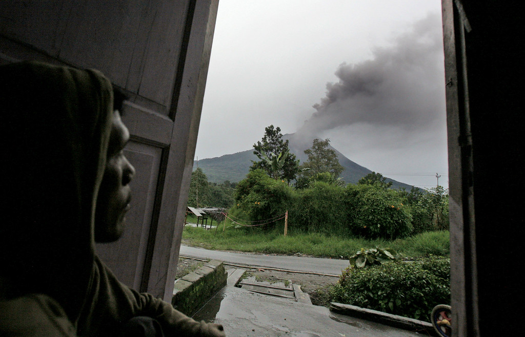 . A man watches Mount Sinabung spewing volcanic ash into the air from inside his house in Tiga Pancur, North Sumatra, Indonesia, Tuesday, Nov. 26, 2013.  (AP Photo/Binsar Bakkara)