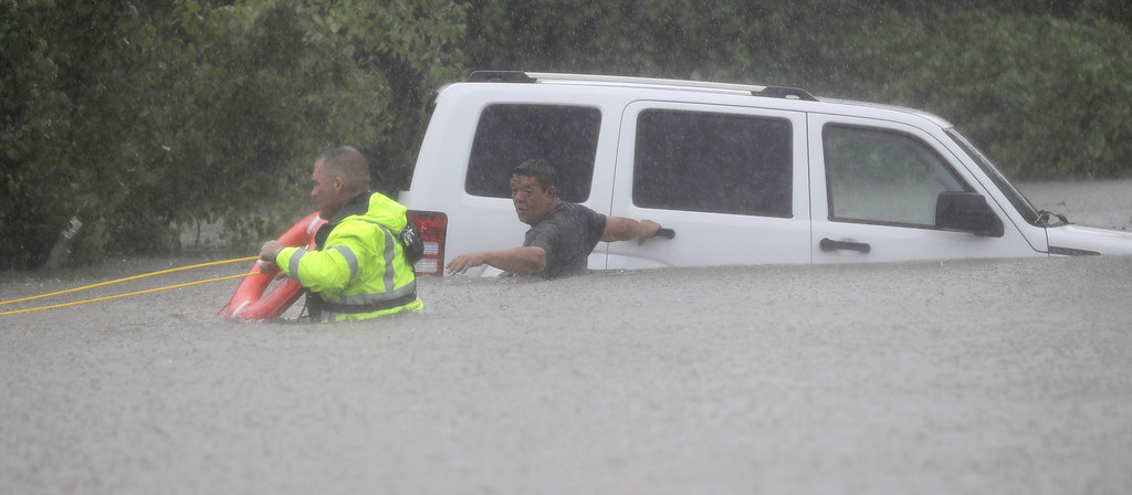 . Wilford Martinez, right, waits to be rescued by Harris County Sheriff\'s Department Richard Wagner after his car got stuck in floodwaters from Tropical Storm Harvey on Sunday, Aug. 27, 2017, in Houston, Texas. (AP Photo/David J. Phillip)