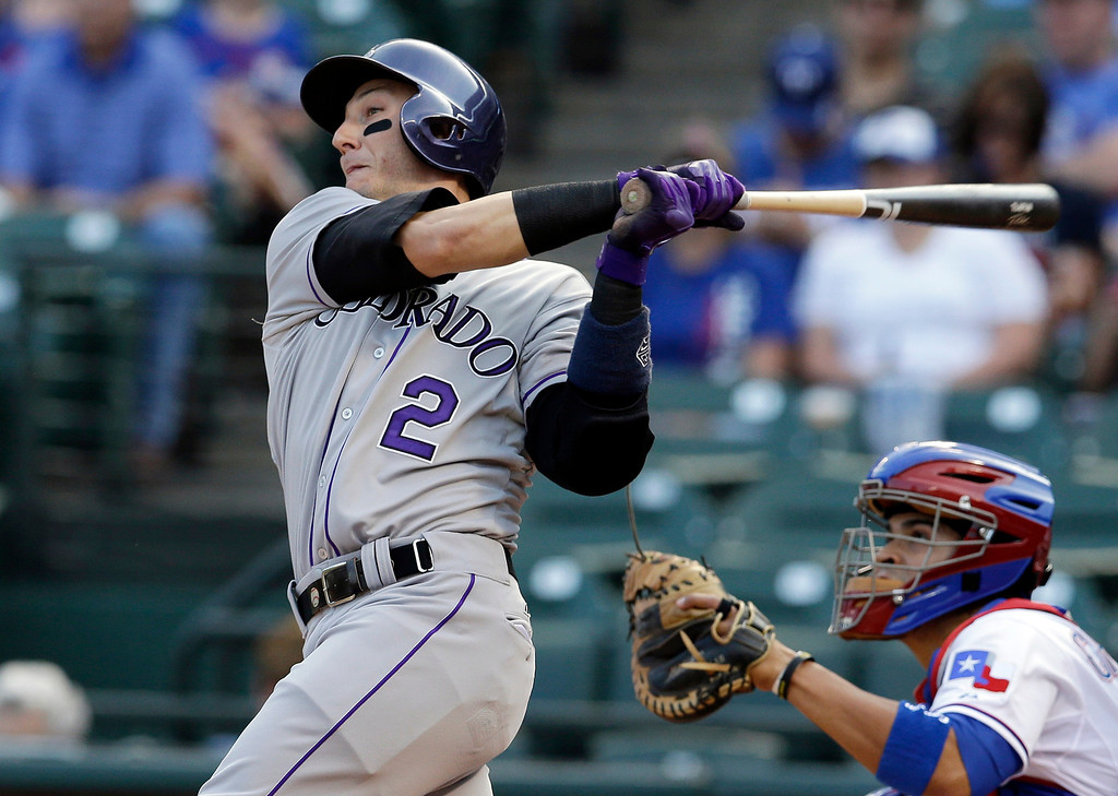 . Colorado Rockies\' Troy Tulowitzki (2) follows through on a single to left as Texas Rangers catcher Robinson Chirinos watches in the first inning of a baseball game, Wednesday, May 7, 2014, in Arlington, Texas. (AP Photo/Tony Gutierrez)