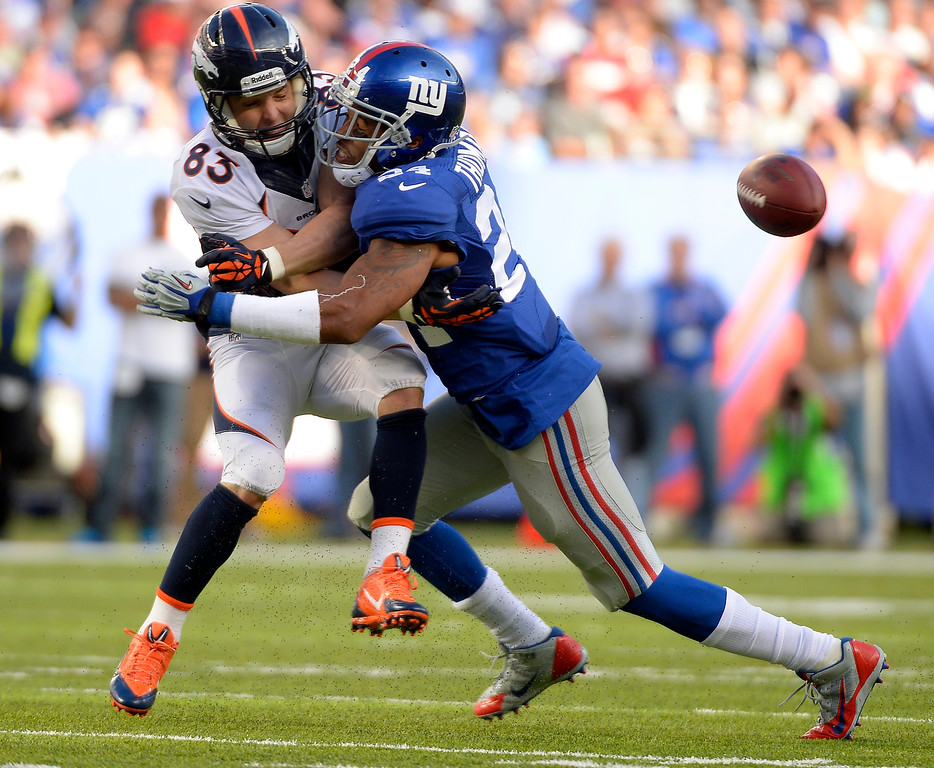 . Denver Broncos wide receiver Wes Welker (83) gets hit hard by New York Giants defensive back Terrell Thomas (24) to jar the ball loose during the second quarter September 15, 2013 MetLife Stadium. The pass was ruled incomplete on the play. (Photo by John Leyba/The Denver Post)