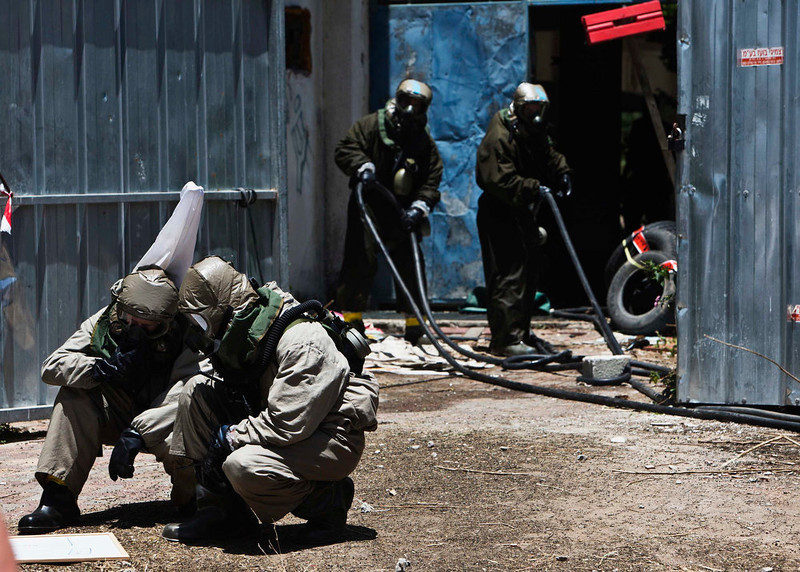 . Israeli soldiers, wearing protective gear, take part in a drill simulating a chemical attack in Azur, near Tel Aviv May 28, 2013. Israel continued on Tuesday with its annual home front defense exercise, launched on Monday, preparing soldiers and civilians for missile attacks. REUTERS/Nir Elias