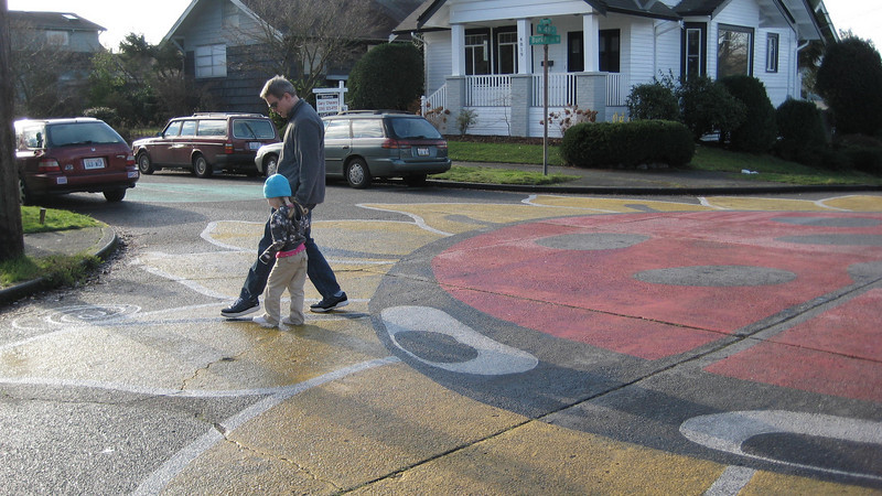 Walking around on the ladybug [A huge ladybug painted in an intersection in the Fremont area].