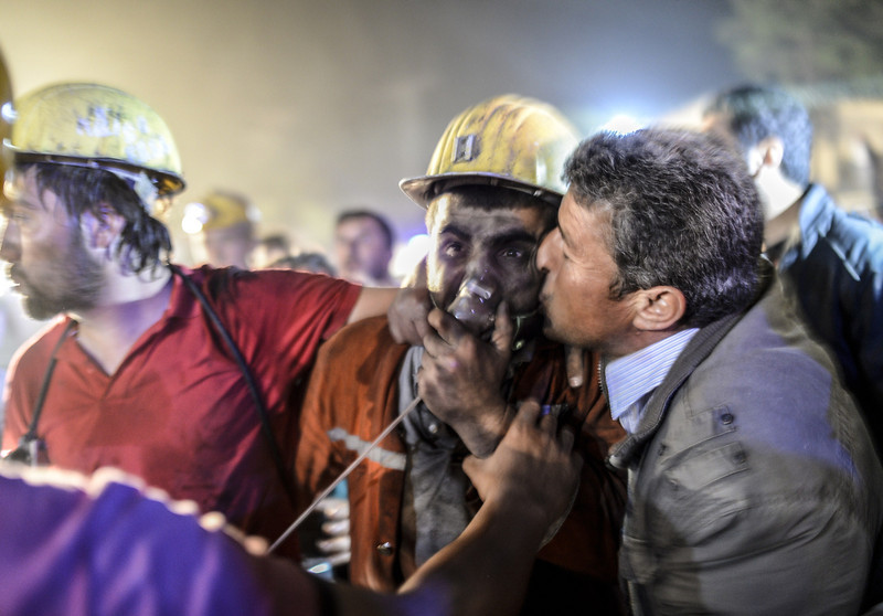 """. A miner celebrates with his father (R) after an explosion on May 13, 2014 in Manisa. Four miner were killed and as many as 300 trapped after a mine collapse in the western Turkish city of Manisa, a local official said.\""""At least 200-300 workers were working in the mine when an electric fault caused an explosion,\"""" the mayor of Soma, a district of Manisa, told private NTV television. (BULENT KILIC/AFP/Getty Images)"""