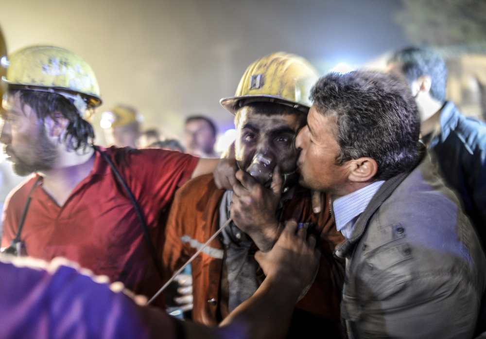 ". A miner celebrates with his father (R) after an explosion on May 13, 2014 in Manisa. Four miner were killed and as many as 300 trapped after a mine collapse in the western Turkish city of Manisa, a local official said.""At least 200-300 workers were working in the mine when an electric fault caused an explosion,\"" the mayor of Soma, a district of Manisa, told private NTV television. (BULENT KILIC/AFP/Getty Images)"