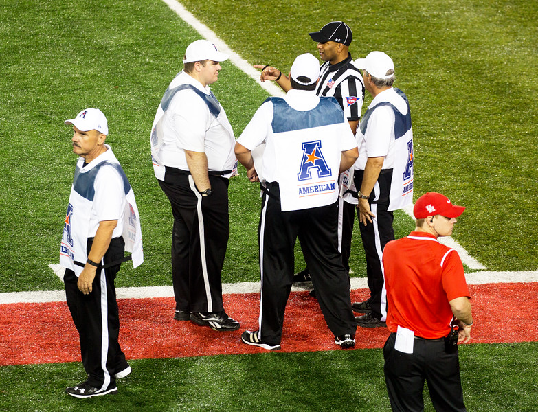 The AAC linesmen talk things over with a referee.