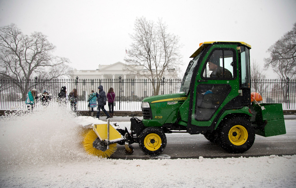 . A Unites States Park Service employee clears snow from in front of the White House as snow continues to fall, Tuesday, Jan. 21, 2014, Washington. (AP Photo/Carolyn Kaster)