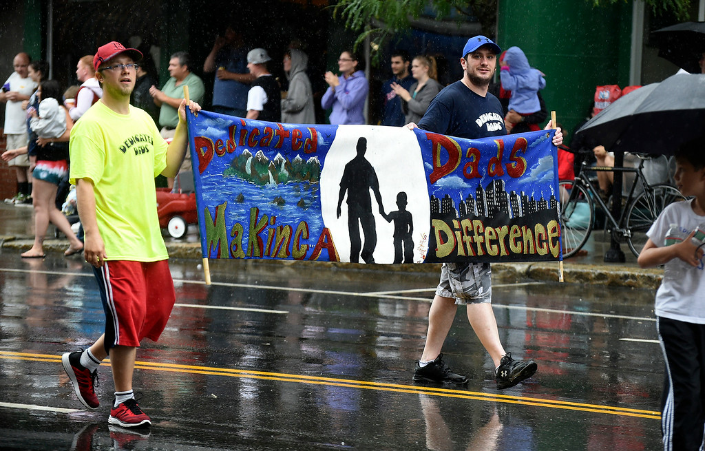 ". Kayla Rice/Reformer Men with ""Dedicated Dads Making a Difference\"" walk down Main St. in the Brattleboro Fourth of July parade on Friday."