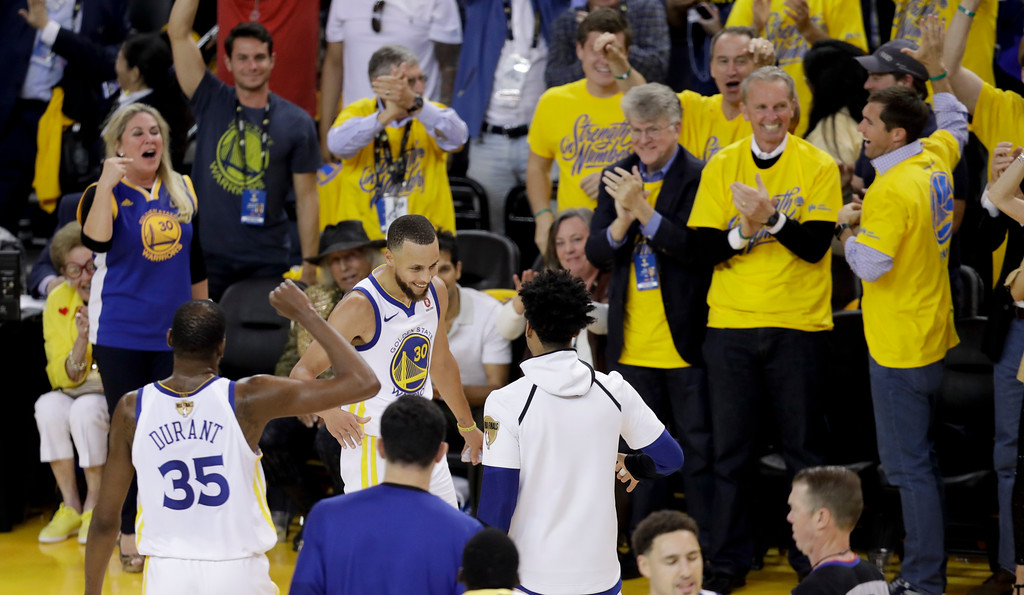 . Golden State Warriors guard Stephen Curry (30) is congratulated by teammates after scoring against the Cleveland Cavaliers during the first half of Game 1 of basketball\'s NBA Finals in Oakland, Calif., Thursday, May 31, 2018. (AP Photo/Marcio Jose Sanchez)