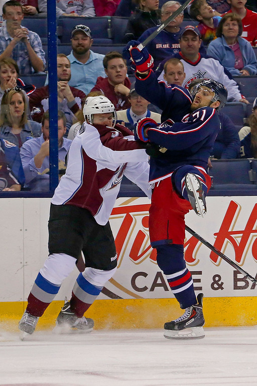 . COLUMBUS, OH - APRIL 1:  Nate Guenin #5 of the Colorado Avalanche checks Nick Foligno #71 of the Columbus Blue Jackets while battling for the puck during the second period on April 1, 2014 at Nationwide Arena in Columbus, Ohio. (Photo by Kirk Irwin/Getty Images)
