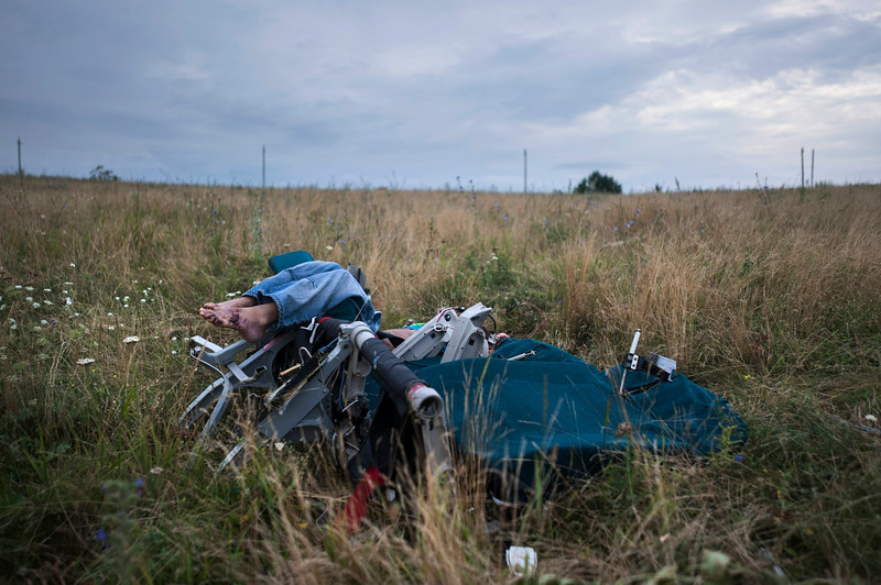 . CAPTION CORRECTION, CORRECTS TO IMPROVE SYNTAX AND CLARITY OF CAPTION - The body of a passenger is partially visible as it lies in a chair at the crash site of Malaysia Airlines Flight 17 near the village of Hrabove, eastern Ukraine, Saturday, July 19, 2014. World leaders demanded Friday that pro-Russia rebels who control the eastern Ukraine crash site of Malaysia Airlines Flight 17 give immediate, unfettered access to independent investigators to determine who shot down the plane. (AP Photo/Evgeniy Maloletka)