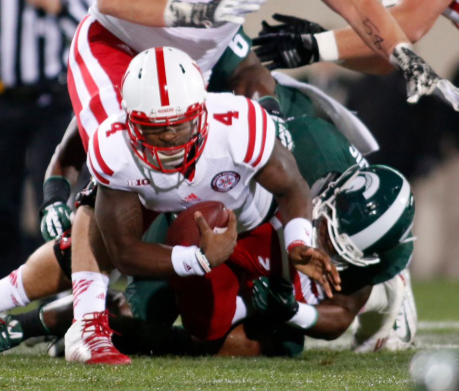 . Nebraska quarterback Tommy Armstrong Jr. (4) is sacked by Michigan State\'s Ed Davis, right, during the first quarter of an NCAA college football game, Saturday, Oct. 4, 2014, in East Lansing, Mich. (AP Photo/Al Goldis)