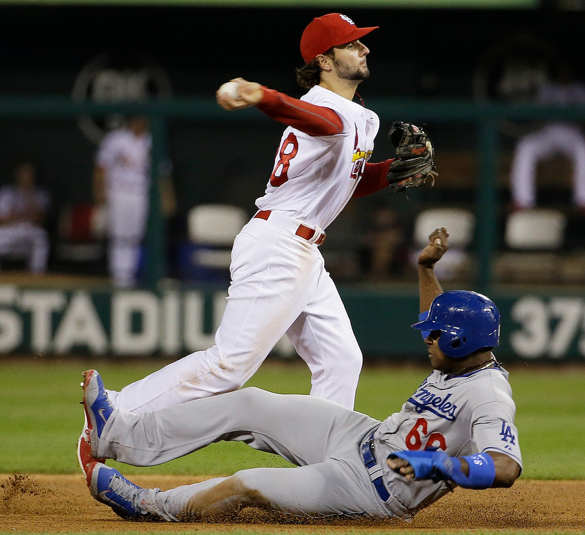 . Los Angeles Dodgers\' Yasiel Puig is out at second as St. Louis Cardinals shortstop Pete Kozma turns a double play on a ball hit by Juan Uribe during the eighth inning of Game 1 of the National League baseball championship series, Friday, Oct. 11, 2013, in St. Louis. (AP Photo/David J. Phillip)