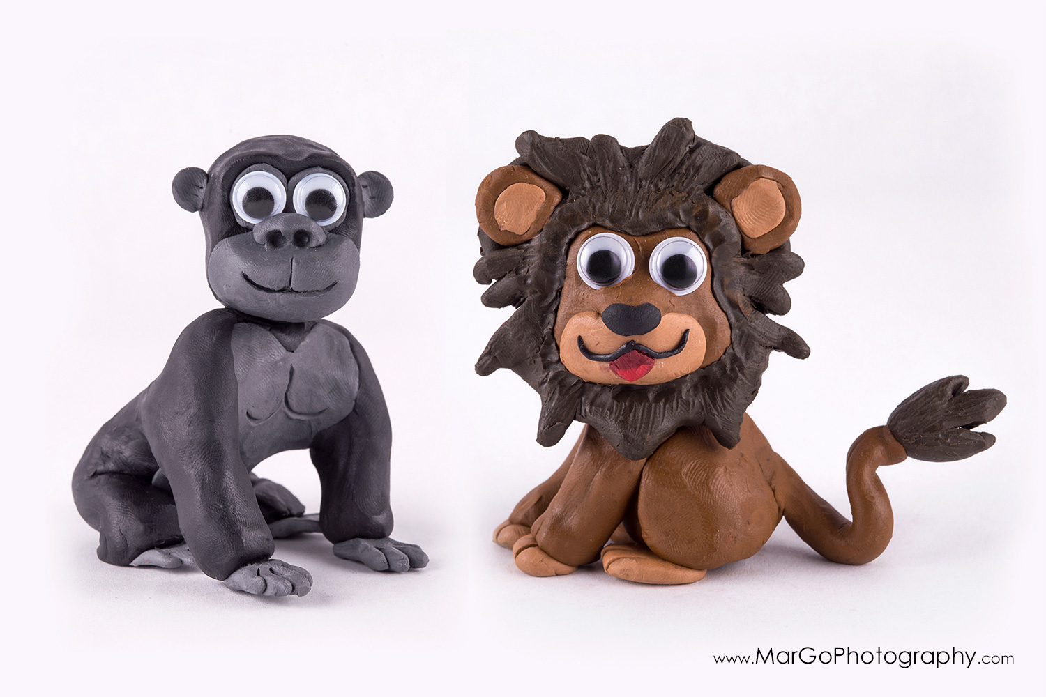 photography of clay grey gorilla and brown lion on white background