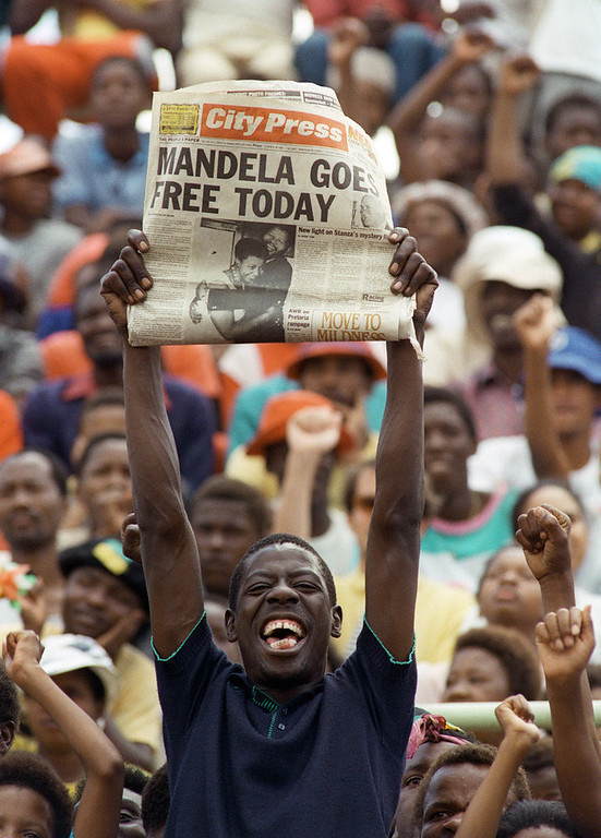 . A jubilant Sowetan holds up 11 February 1990 in Soweto a newspaper announcing the release of anti-apartheid leader and member of the African National Congress (ANC) Nelson Mandela, at a mass ANC rally. South African President de Klerk lifted 02 February the 30-year-old ban on the ANC and the South African Communikst Party, and 11 February, Nelson Mandela walked out of Victor Vester prison, near Cape Town, after 26 year since he  was sentenced to life imprisonment. (Photo credit should read TREVOR SAMSON/AFP/Getty Images)