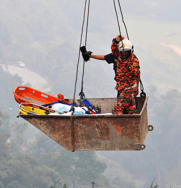 . Malaysian emergency services personnel use a crane to rescue passengers  after a bus carrying tourists and local residents fell into a ravine near the Genting Highlands, about an hour\'s drive from Kuala Lumpur, Malaysia, Wednesday, Aug. 21, 2013.   (AP Photo)