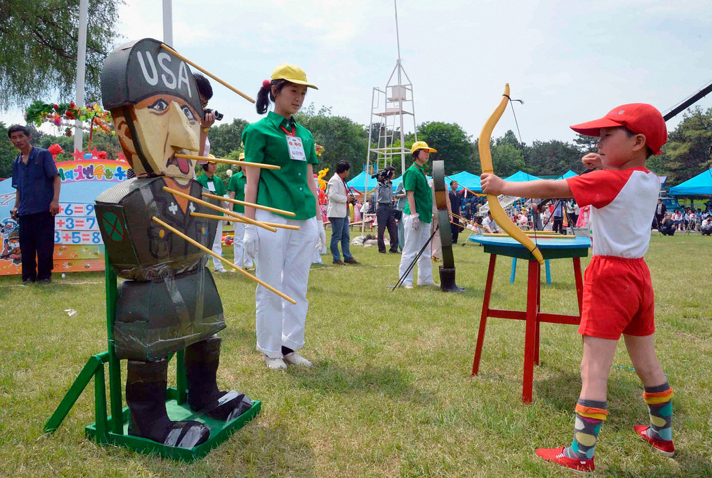 . A child shoots an arrow at an effigy of a U.S. soldier at an amusement park in Pyongyang to mark International Children\'s Day, in this photo taken by Kyodo June 1, 2013.    Mandatory Credit. REUTERS/Kyodo