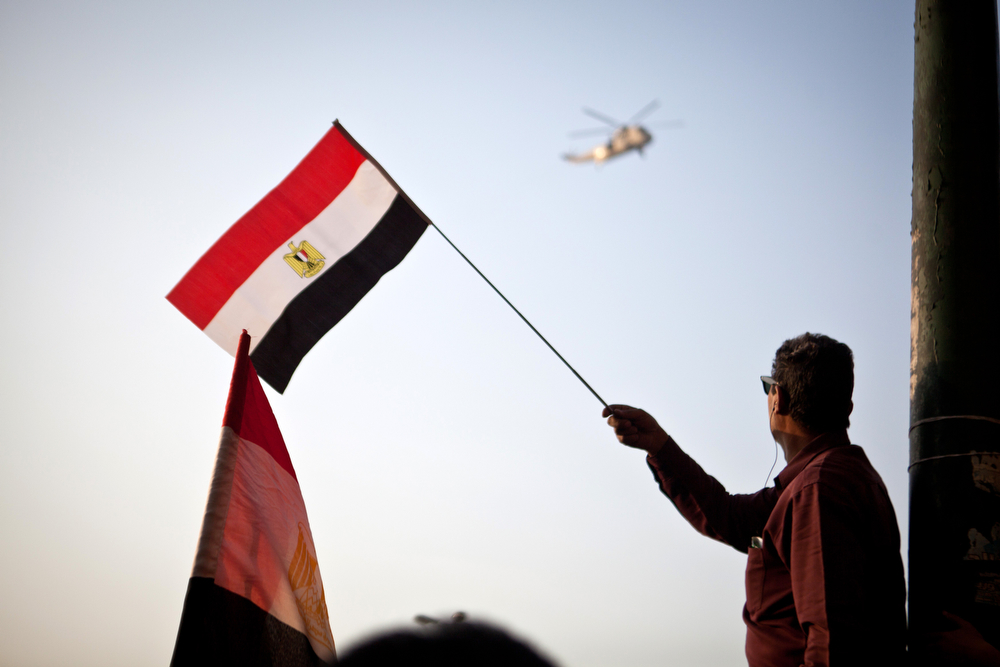 . An Egyptian man waves the national flag as an Army helicopter hovers over in Cairo\'s Tahrir Square during a rally marking the anniversary of the 2011 Arab Spring uprising on January 25, 2014. A spate of deadly bombings put Egyptian police on edge as supporters and opponents of the military-installed government take part in rival rallies for the anniversary of the 2011 Arab Spring uprising.(VIRGINIE NGUYEN HOANG/AFP/Getty Images)