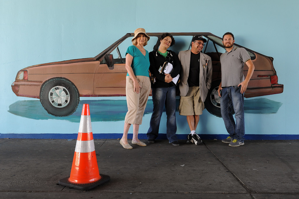 """. Jan Brown, from left, Erika Tachet, Joe Nicoletti and   Elijah Flores at the restoration of the mural \""""Panorama: G.M. Recollections from the Past,\"""" on Van Nuys Boulevard in Panorama City, Thursday, June 20, 2013. The original mural was painted by Alfredo Diaz Flores in 1998 and pays homage to the General Motors plant that used to be near the mural site. (Michael Owen Baker/Staff Photographer)"""