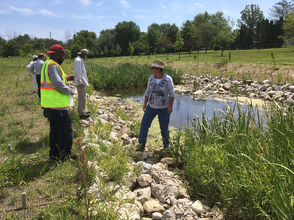 . Richard Payerchin - The Morning Journal <br> Lyn Ickes, watershed specialist in the Lorain County Community Development Department, stands on the rocks as she speaks to members of the Black River Civilian Conservation Corps at the Willow Creek restoration site in the Eaton Township Community Park on June 28, 2017.