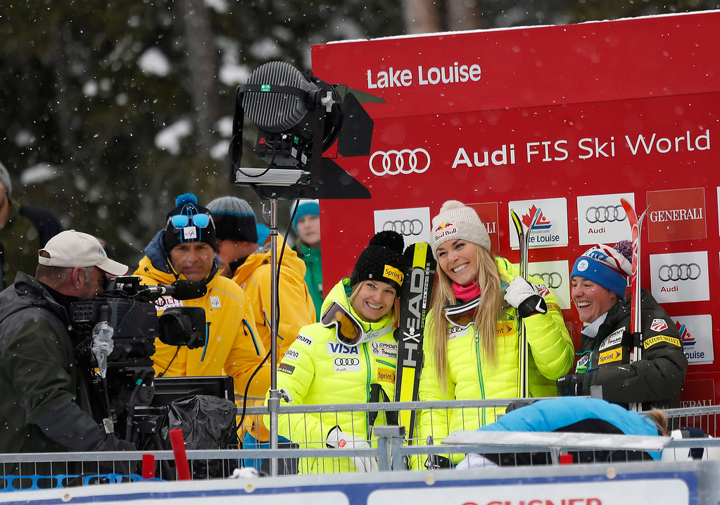 . From left, third-place finisher Julia Mancuso (8), first-place finisher Lindsey Vonn (12) and  second-place finisher Stacey Cook (5), all from the United States, react in the finish area following the women\'s World Cup downhill ski race in Lake Louise, Alberta, Saturday, Dec. 6, 2014. (AP Photo/The Canadian Press, Jeff McIntosh)