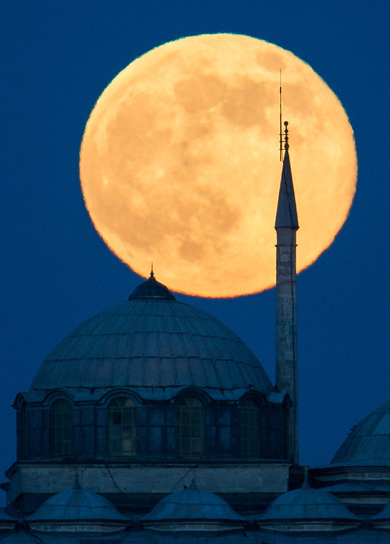 ". A ""super moon\"" rises behind a building of the Topkapi Palace in Istanbul, Turkey on Sunday, June 23, 2013. The moon, which will reach its full stage on Sunday, is expected to be 13.5 percent closer to earth during a phenomenon known as a \""super moon\"". The \""super moon\"" happens only once this year as the moon on its elliptical orbit is at its closest point to earth.  (AP Photo/Gero Breloer)"