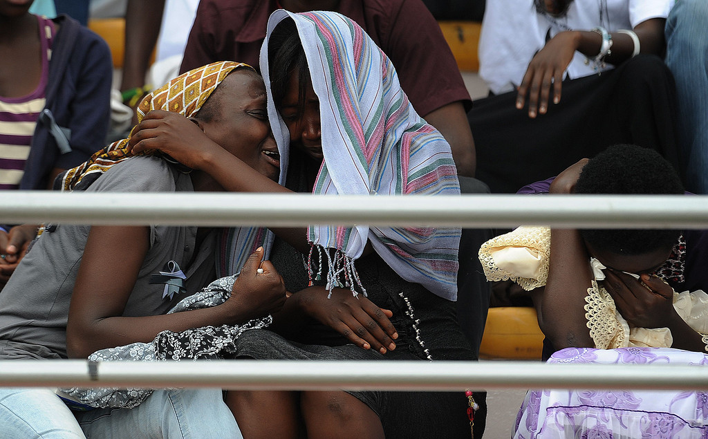 """. Women cry at the Amahoro stadium in Kigali, on April 7,2014, as they attend a ceremony marking the 20th anniversary of Rwanda\'s genocide. Rwandan President Paul Kagame took a thinly-veiled swipe at France on April 7, saying it was impossible to \""""change the facts\"""" about the genocide 20 years ago.   AFP PHOTO / SIMON MAINA/AFP/Getty Images"""