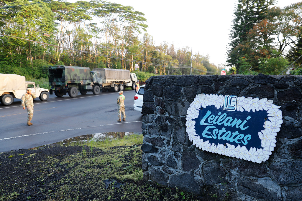 . National guardsmen and police stand at the entrance to Leilani Estates, Friday, May 4, 2018, in Pahoa, Hawaii. A mandatory evacuation for the area as declared by the state. Due to unsafe conditions in the area from the recent lava eruption, residents who evacuated could not return to their homes Friday. (AP Photo/Marco Garcia)
