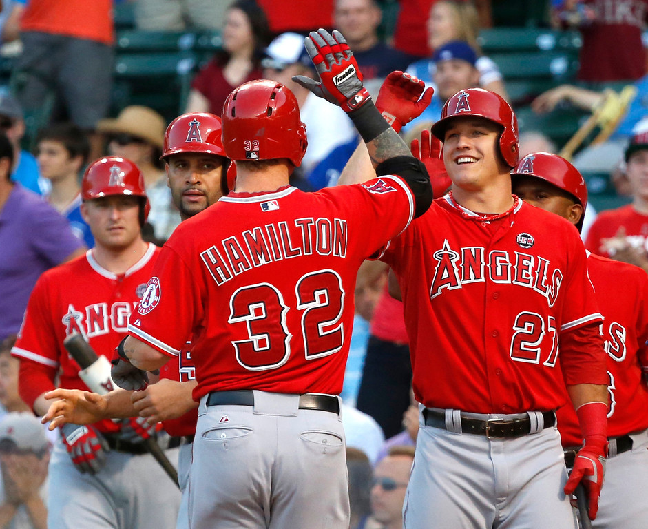 . Los Angeles Angels\' Josh Hamilton (32) is greeted at home by Mike Trout (27) and Albert Pujols, center left, after hitting a three-run home run off Chicago Cubs starting pitcher Jeff Samardzija during the first inning of an interleague  baseball game Wednesday, July 10, 2013, in Chicago. (AP Photo/Charles Rex Arbogast)