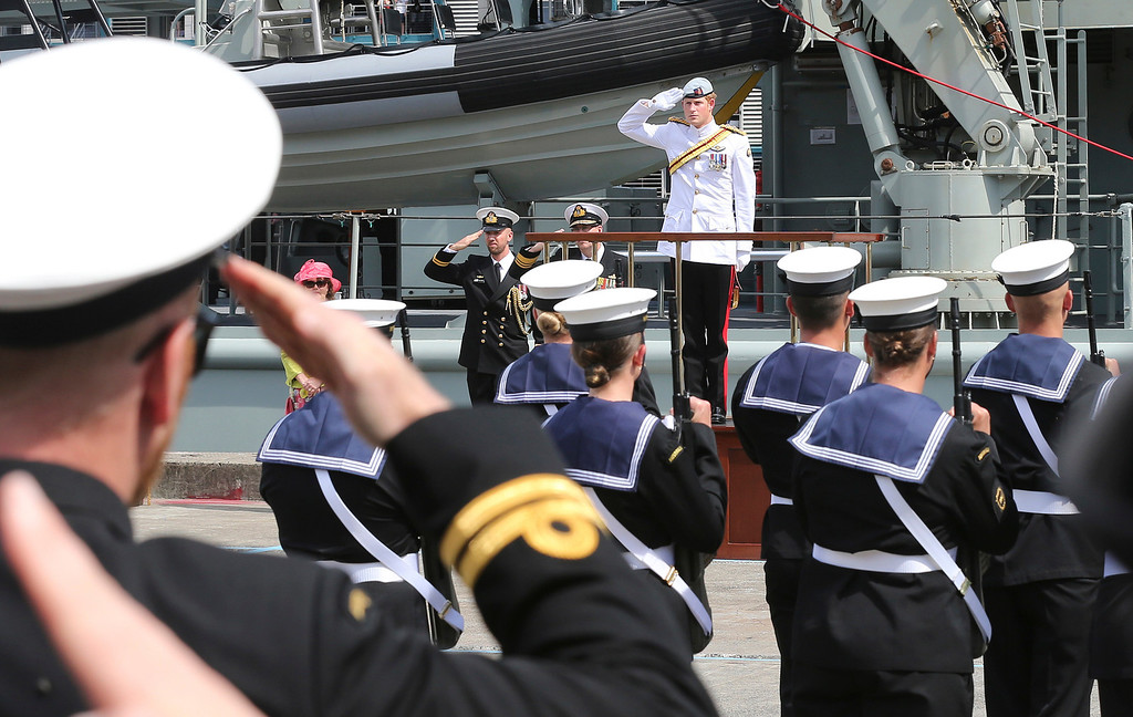 . Britain\'s Prince Harry, center in the background, receives a royal salute from the honor guard at Garden Island Naval base in Sydney, Australia, Saturday, Oct. 5, 2013 before boarding HMAS Leeuwin to view the International Fleet review. The prince glided through Sydney\'s sun-dappled harbor aboard the navy ship on Saturday, as thousands of people crowded the shoreline to catch a glimpse of royalty and celebrate the centenary of the fledgling Australian navy fleet\'s first arrival to the famed waterway. (AP Photo/Rob Griffith)