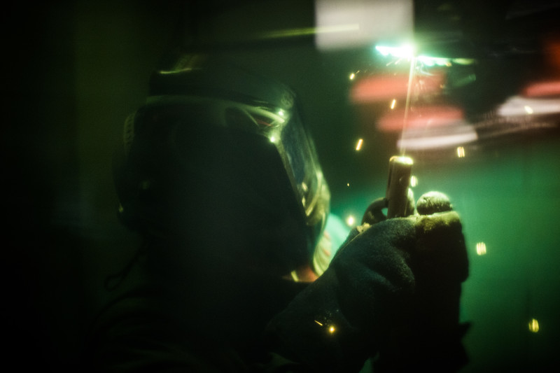A man wearing a welding mask working.